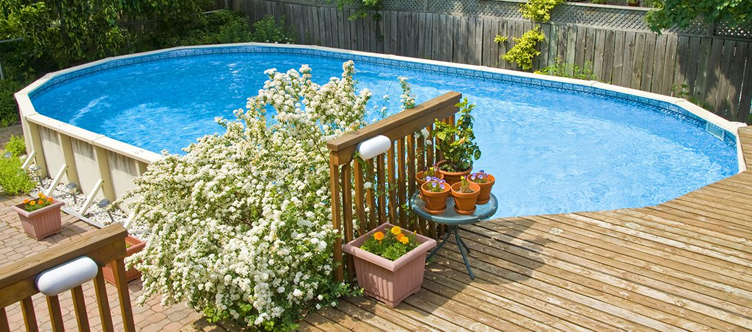 Newly installed pool with a deck and plants surrounding one side
