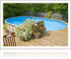 Swimming pool installed in backyard next to a deck and surrounded by plants